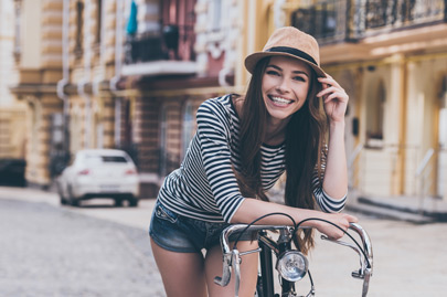 Beautiful young woman leaning at her bicycle and smiling while standing outdoors