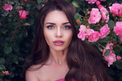 Beauty romantic portrait of young pretty beautiful woman with long curly hair posing between pink roses