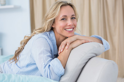 Cheerful pretty blonde sitting on couch at home in the living room