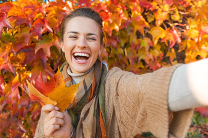 Cheerful young woman with autumn leafs in front of foliage making selfie