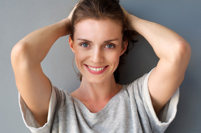 Happy mid adult woman smiling with hands in hair