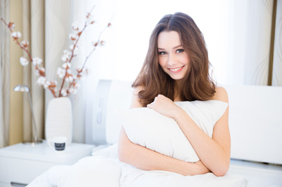 Sensual smiling young woman sitting on bed and hugging white pillow