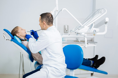 Serious dentist sitting in semi position while examining his patient