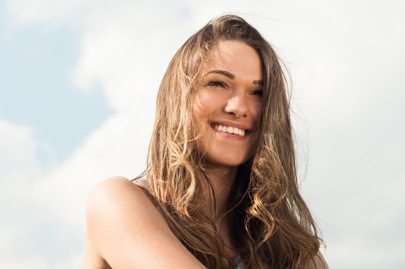 smiling female relaxing in the nature on warm sunny day with copyspace