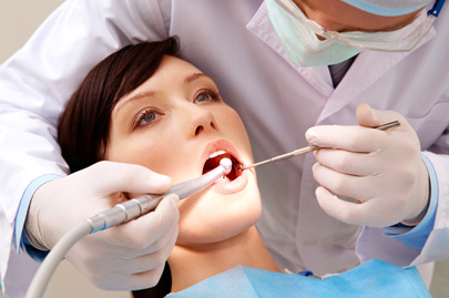 Young woman keeping her mouth open while dentist examining it
